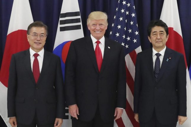 From left to right, South Korean President Moon Jae-in, U.S. President Donald Trump and Japanese Prime Minister Shinzo Abe in Hamburg, Germany, in 2017. Trump's approach to alliances is affecting Korea, Japan ties, U.S. analysts said Thursday. File Photo by Yonhap/EPA