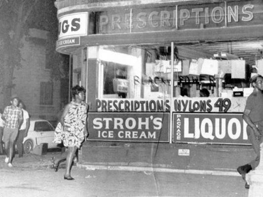 People rush past a drug store that is being looted on Detroit's West Side during the civil unrest of 1967. Black Power has been written on one of the windows. UPI Telephoto