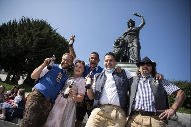 Visitors celebrate in lieu of Oktoberfest on the steps of the Bavaria-Statue on the Theresienwiese in Munich, Germany, on September 19, 2020. Both the 2020 and 2021 events were canceled due to the coronavirus pandemic. File Photo by Lukas Barth Tuttas/EPA-EFE