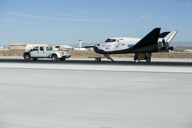 A pickup truck pulls the Sierra Nevada Corporation (SNC) Dream Chaser flight vehicle through range and taxi tow testing Aug. 2. Credit: NASA/Ken Ulbrich