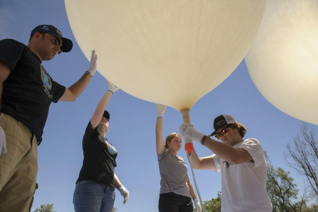 Montana State University students fill a pair of high-altitude balloons with helium in preparation for a launch. Photo by Kelly Gorham/Montana State University