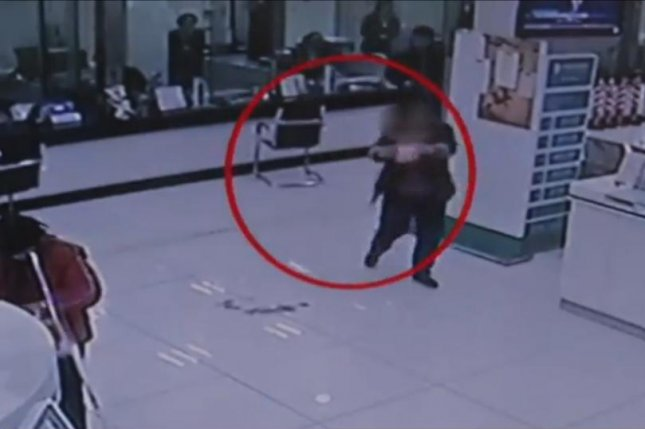 A 60-year-old woman dumps feces on the floor at the Agricultural Bank in Nanjing one day after arguing with workers. Newsflare video screenshot