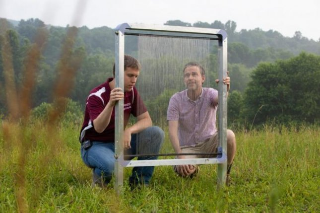 Virginia Tech researchers Jonathan Boreyko and Brook Kennedy inspect their fog harp at Kentland Farm, where they pitted the water harvesting device against similar devices. Photo by Peter Means/Virginia Tech