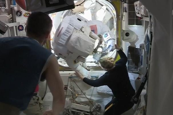 NASA astronaut Kate Rubins helps Victor Glover back into the International Space Station after he and Mike Hopkins completed their spacewalk Wednesday. Photo courtesy of NASA