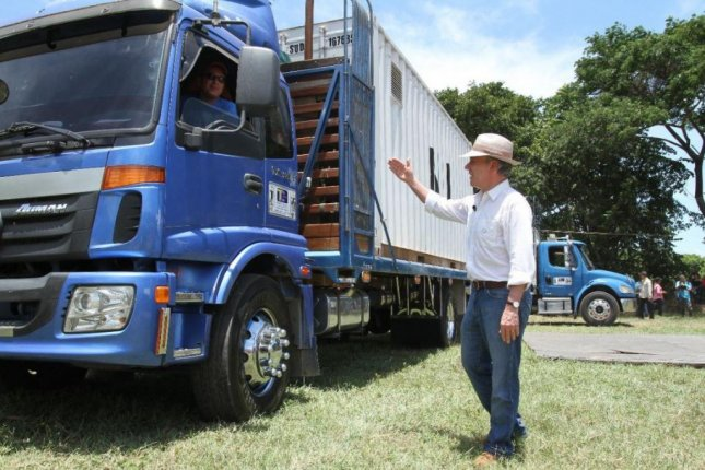 Colombian President Juan Manuel Santos waves at a trucker removing a container of FARC weapons from a disarmament zone on Tuesday. Photo courtesy Juan Manuel Santos