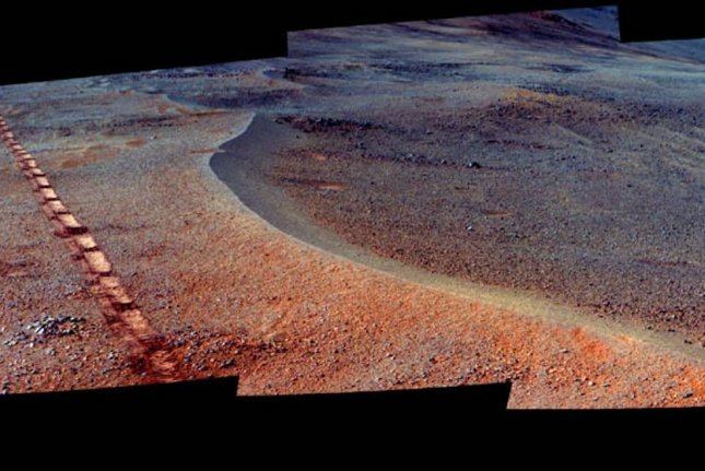 An enhanced color image shows the tire tracks of the Opportunity rover running beside the edge of the newly discovered crater. Photo by NASA/JPL-Caltech/Cornell Univ./Arizona State Univ.