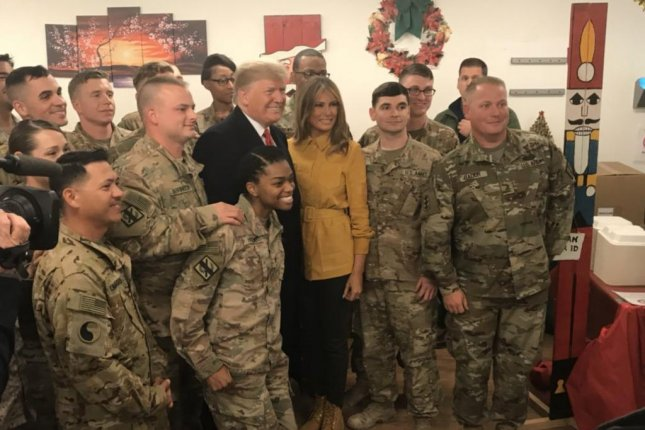 President Donald Trump and first lady Melania Trump pose with troops stationed in Iraq on Christmas