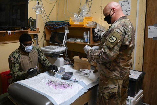 U.S. Navy Hospital Corpsman 2nd Class Quentin Denzel Foley (left), a preventive medicine technician with the Expeditionary Medical Unit assigned to Camp Lemonnier and Sgt. 1st Class Bob Godes (right), the surgeon cell senior enlisted leader with Combined Joint Task Force- Horn of Africa (CJTF-HOA), prepare syringes the COVID vaccine at Camp Simba, Kenya, March 18. Photo by Taylor Davis/U.S. Air Force