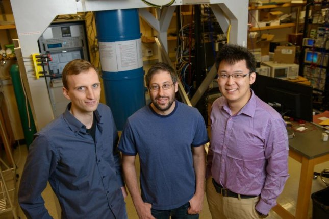 A trio of researchers at the University of Chicago, have managed to incorporate electron-trapping technology into a resonator used in quantum computer circuitry. Grad students Gerwin Koolstra and Ge Yang, pictured left and right, stand on either side of David Schuster, an assistant professor in physics. Photo by Rob Hart