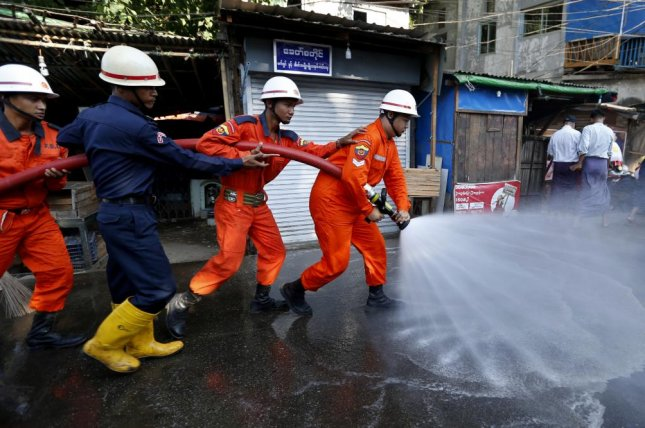 Firefighters spray water at a local market amid concerns over the spread of the novel coronavirus in Yangon, Myanmar on Friday. The country is warning of an increase in coronavirus infections. Photo by Nyein Chan Naing/EPA-EFE