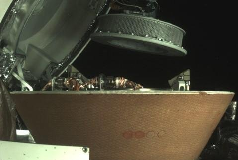 At left, the OSIRIS-REx collector head -- after recovering a sample from an asteroid -- hovers over the Sample Return Capsule after being moved into the proper position for capture, and the right image shows the collector head secured onto the capture ring in the SRC. Photo by NASA/Goddard/University of Arizona/Lockheed Martin