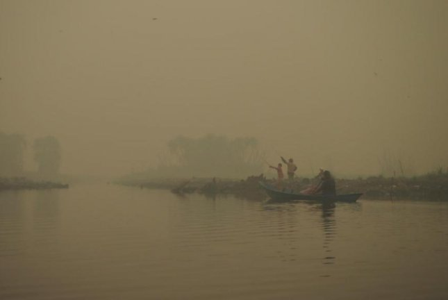 Local fishers paddle through the smoky haze from peatlandfires in Central Kalimantan, Indonesia. Photo by Suzanne Turnock/Borneo Nature Foundation