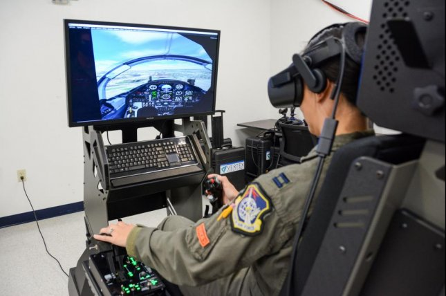 """Air Force Capt. Christine """"Switch"""" Durham, 19th Air Force Detachment 24, director of staff, uses the Joint Immersive Training System at Joint Base San Antonio-Randolph, Texas, Monday. A replica of the cockpit can be seen on the flight simulator monitor. Photo byAryn Lockhart/U.S. Air Force"""