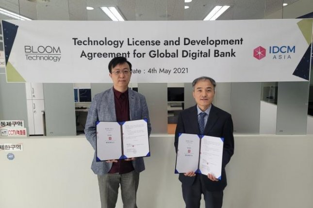 Bloom Technology CEO Lee Sang-yoon (L) holds an agreement with IDCM Asia CEO Joseph Lee after agreeing to cooperate to start a blockchain-based digital banking platform on May 4 at IDCM Asia's head office in Seoul. Photo courtesy of Bloom Technology