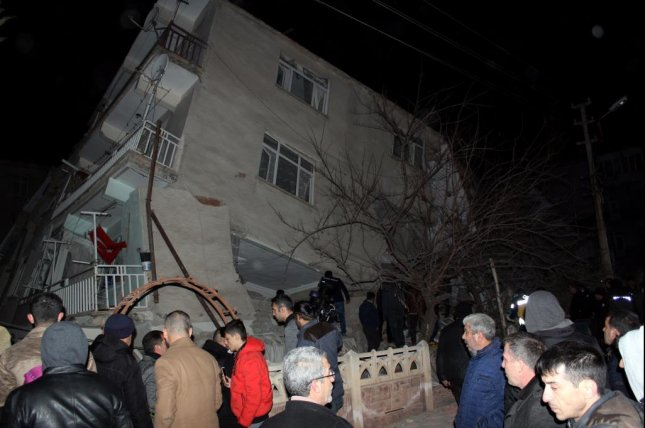 Residents of Elazig, Turkey, stand before a damaged building after a magnitude-6.5 earthquake struck the region on Friday. The government reported at least four deaths. Photo courtesy of EPA-EFE/STR