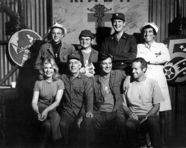 Cast photo from M*A*S*H for 1977. Front row from left: Loretta Swit, Harry Morgan, Alan Alda and Mike Farrell. Back row from left: William Christopher, Gary Burghoff, David Ogden Stiers and Jamie Farr. Photo courtesy of CBS Television via Wikimedia Commons