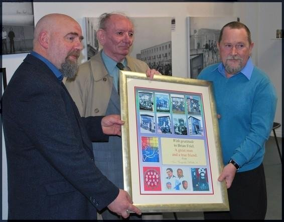 Irish writer Brian Friel (center) receives an honor on his 80th birthday from The Bogside Artists collective. Photo by Thebogsideartists/Wikimedia