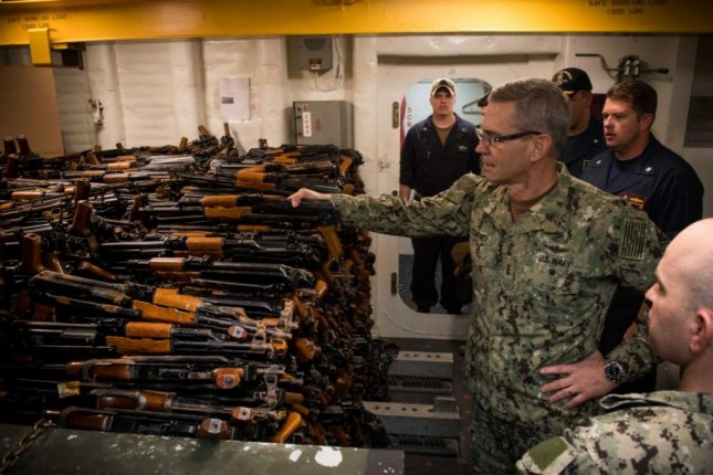 Navy Vice Adm. Scott Stearney, aboard the USS Jason Dunham in the Strait of Hormuz, examines 2,500 weapons Thursday that were seized in an August raid. Photo courtesy CS3C Jonathan Cray/U.S. Navy