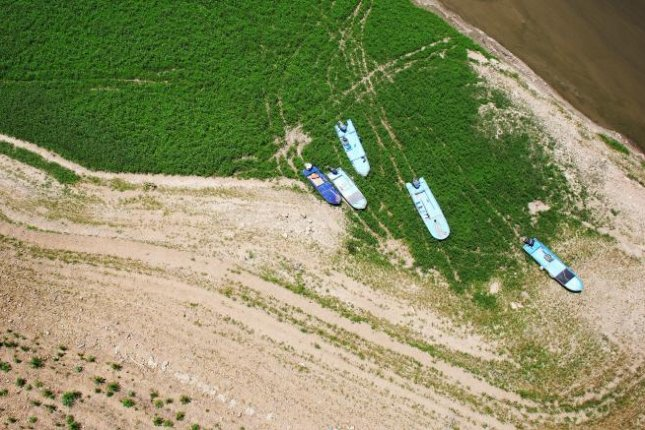 An aerial photo taken on Wednesday above Soyang Lake in Gangwon province, South Korea, showed boats that once tugged along the waters were stranded atop a field of green weeds. Photo by Yonhap