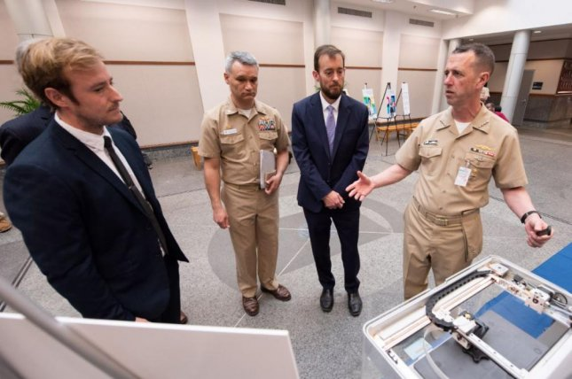 Chief of Naval Operations Adm. John Richardson, R, explains 3D printing at the Naval Information Warfare Center in Charleston, S.C., on April 12, 2019. The Navy announced a contract valued potentially at $968.1 million, for C4ISR installation support, to eight companies on Thursday. Photo by Joe Bullinger/U.S. Navy