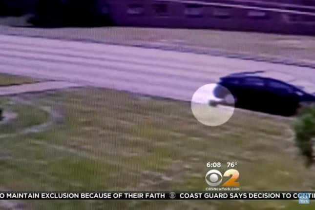 Employees with ATMForUs.com leave the bag containing $141,000 at the side of a road, where it was soon picked up by a passenger in a white work van. CBS New York/YouTube video screenshot