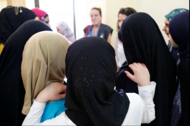Syrian and Lebanese girls huddle round in a group discussion about early marriage at a community center in southern Lebanon in 2014. Photo by Russell Watkins/Department for International Development