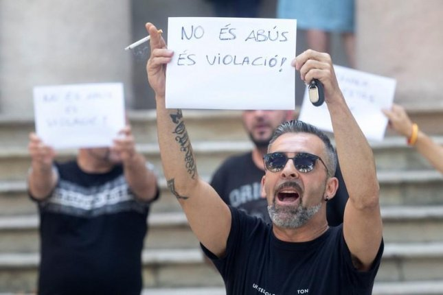 The uncle of a rape victim holds up a banner that reads It is not sexual abuse, it is rape in Spanish. He's protesting the court's decision to convict five men on lesser sexual abuse charges rather than rape in the case of a 14-year-old girl. Photo by Quique Garcia/EPA-EFE