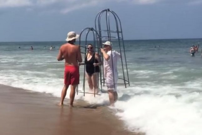 Sandi and Scott Bergman speak with a lifeguard about their homemade shark cages at a beach on North Carolina's Outer Banks. Jordan Cutrell/YouTube video screenshot