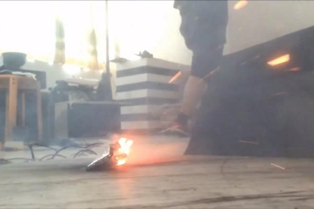 A Samsung Galaxy Note 7 bursts into flames after being struck with a hammer. Screenshot: Storyful