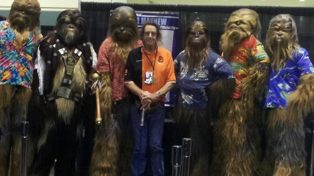 Peter Mayhew with his light saber cane and a group of wookies. (Twitter)