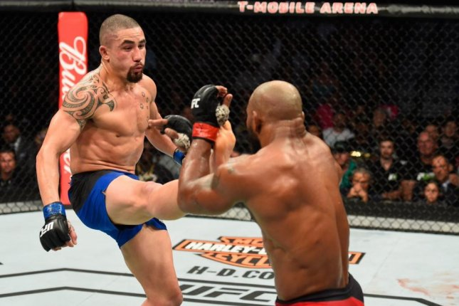 Robert Whittaker (left) was injured by a Yoel Romero (right) kick in the first round of their UFC 213 main event on Saturday night at T-Mobile Arena. But he persevered and took the UFC interim middleweight belt after a grueling five-round battle. Photo courtesy of UFC/Twitter