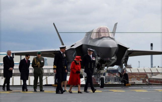 Queen Elizabeth II, foreground in red, visited the aircraft carrier bearing her name before the ship and its strike group departed Portsmouth, Britain, for a seven-month deployment. Photo courtesy of Royal Navy/Facebook