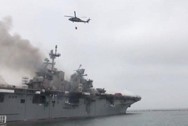 U.S. Navy helicopters assist in fighting a fire that has been burning on the SS Bonhomme Richard since Sunday morning. Image via Naval Surface Forces/Twitter