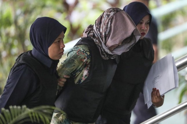 Doan Thi Huong (C), a Vietnamese national who was detained in connection with the death of Kim Jong Nam, is escorted by Malaysian police officers as she arrives at the Shah Alam High Court, in Shah Alam, Malaysia, on Thursday. Photo by Fazry Ismail/EPA-efe