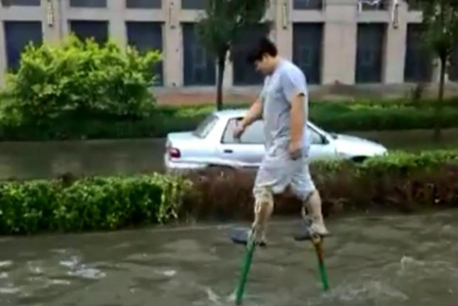 A man in Wuhan, China, uses stilts to stay above floodwaters. Screenshot: Newsflare