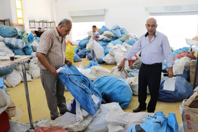 Palestinian officials sort through dozens of bags of delayed mail after it was released by Israel. Photo courtesy of the Palestinian communications ministry