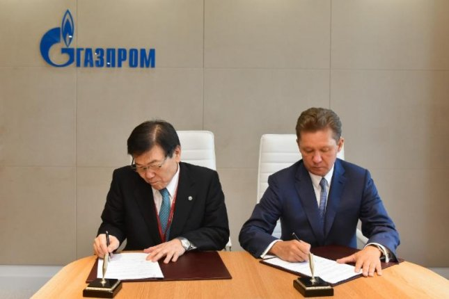 Masami Iijima (L), chairman of the board of directors of Mitsui & Co., Ltd., signs a framework agreement on liquefied natural gas with Alexei Miller, the chairman of Russia's Gazprom. Photo courtesy of Gazprom.
