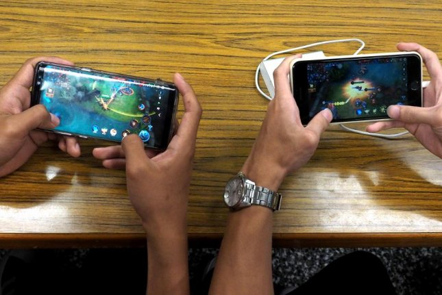 Students play video games on smartphones. Photo by David Chang/EPA-EFE