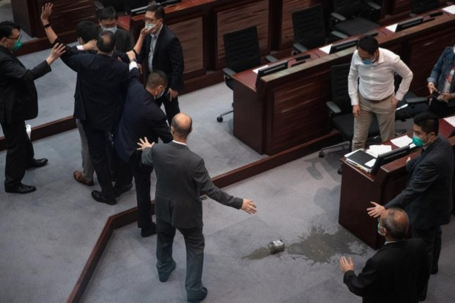 Pan-democrat lawmaker Ted Hui (L) raises his arms after spilling a foul-smelling liquid on the floor of the conference room during the third reading of the national anthem bill at the Legislative Council in Hong Kong on Thursday.  Photo by Jerome Favre/EPA-EFE