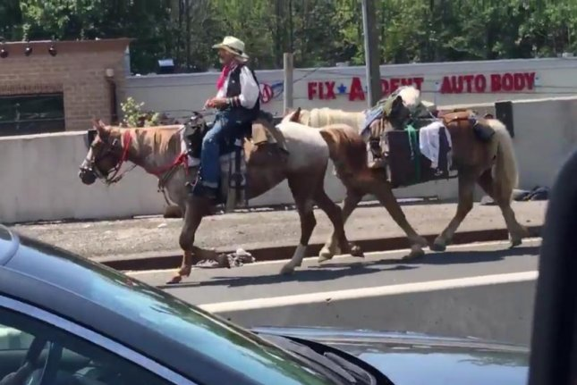Traffic on New York's Outerbridge Crossing was brought to a stand-still Monday morning when a man in cowboy clothes took two horses across the bridge. Screenshot: @calvs88/Twitter