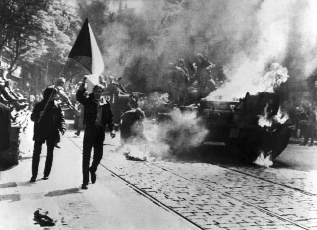 During the Soviet invasion of Czechoslovakia, Czechoslovaks carry their national flag past a burning tank in Prague. Photo courtesy CIA
