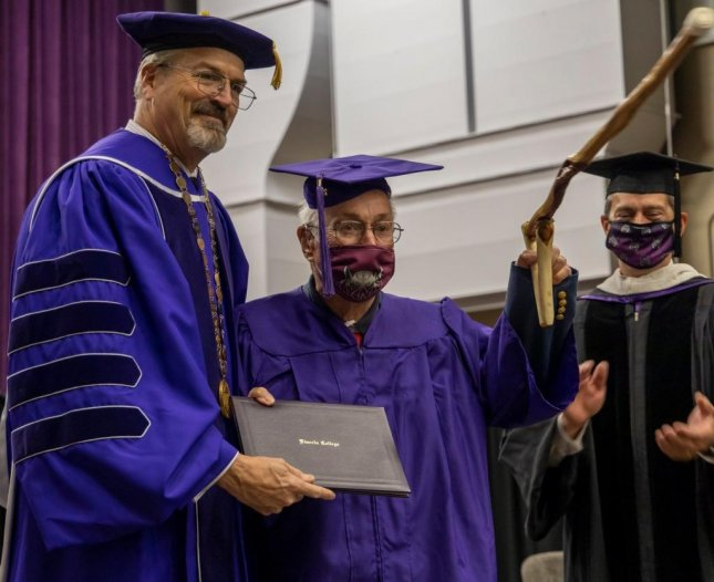 Lincoln College President David Gerlach presentsBill Gossett, 97, with hisAssociate of Arts degree nearly 80 years after the World War II veteran began his college education. Photo courtesy of Lincoln College