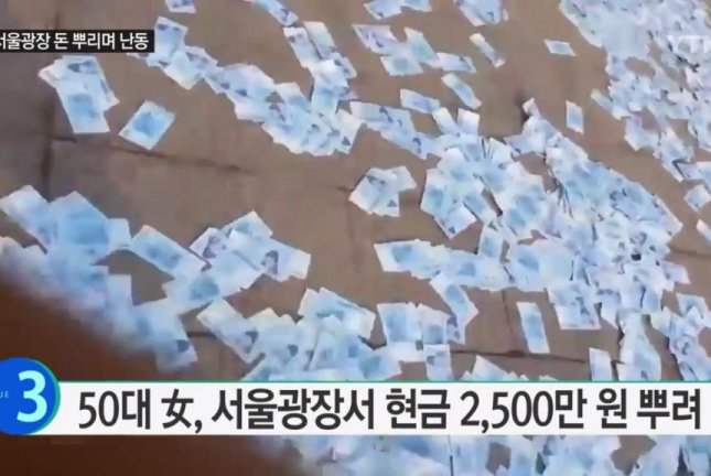 A woman in South Korea threw nearly $20,000 onto a public walkway, but no one was seen picking up any of the cash. Screenshot: YTN News/YouTube