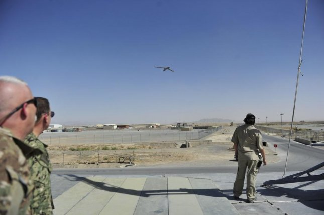 Rear Adm. Luke McCollum, vice commander, U.S. Naval Forces Central Command, second from left, and ScanEagle Theater Chief Capt. Clay Allen, ScanEagle Guardian Eight Site, left, watch a ScanEagle approach for recovery at Train, Advise and Assist Command South based at Kandahar Airfield. Photo by Lt. Kristine Volk/U.S. Navy