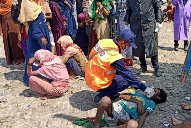 Rohingya migrants receive first aid and food after being rescued at sea, near Cox's Bazar, Bangladesh, Thursday. Activists fear hundreds of Rohingya refugees remain stuck at sea as more countries cite the COVID-19 pandemic as a reason to refuse them entry. Photo courtesy of Bangladesh Coast Guard