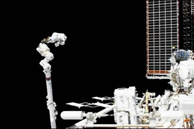 Luca Parmitano of the European Space Agency is shown attached to the Canadarm during the first of a series of spacewalk missions aimed at repairing the Alpha Magnetic Spectrometer. Photo by NASA TV