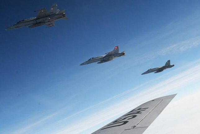Four Swiss F-18 Hornets fly alongside a U.S. Air Force KC-135 Stratotanker, assigned to the 100th Air Refueling Wing RAF Mildenhall, England, after receiving fuel over Germany on Oct. 20, 2017. Photo by Senior Airman Justine Rho/U.S. Air Force