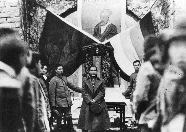 Sun Yat-sen in 1912 at one of the historic crossroads with the Five Races Under One Union flag and the Blue Sky with a White Sun flag. File Photo courtesy Wikimedia Commons