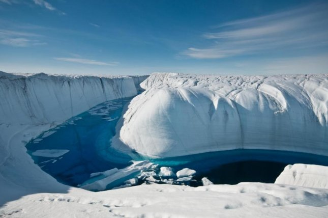 A stream of meltwater carves through Greenland's ice sheet, part of what researchers say is an accelerating rate of ice loss globally. Photo by Ian Joughin/Leeds University