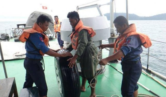Myanmar navy personnel stand with what they said is a wheel from a military plane which is believed to have gone down in the Andaman Sea on Wednesday. The bodies of 10 people, of 122 aboard, have been recovered thus far, a military statement said. Photo courtesy of Myanmar military